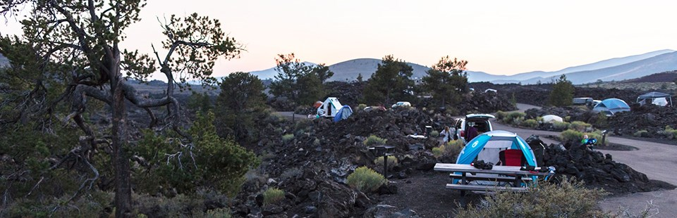 A tent and a picnic table within the Lava Flow Campground.