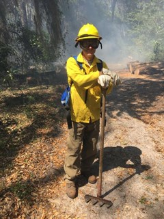 fire fighter in nomex gear with fire rake