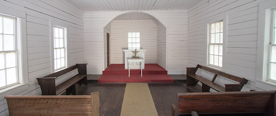 Single room church with white walls, wood floor, altar and pews