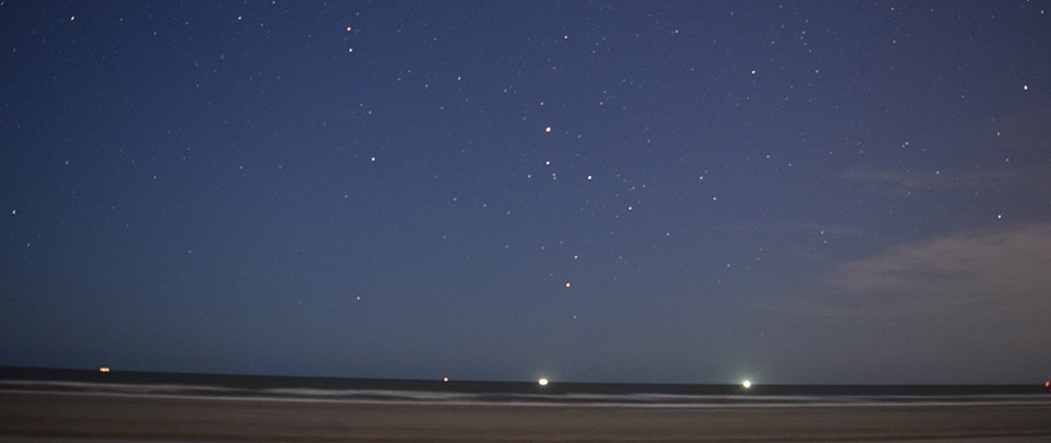 beach view at night under a starry sky with boat lights on the horizon
