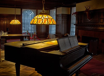 Room with dark oak wall coverings and coffered ceiling; piano under glass shaded chandeliers; deer head on wall