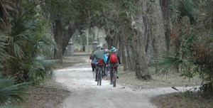 two visitors ride bikes on sandy road under tree canopy