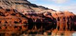 Red cliffs descend into the water of Bighorn Canyon