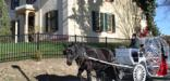 A horse-drawn carriage passes in front of the Taft house