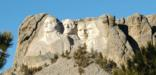 Mount Rushmore, Washington, Jefferson, T. Roosevelt, Lincoln framed by ponderosa pine trees under a bright blue sky.
