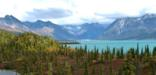 Fall colors dot a landscape with towering mountain peaks and turquoise lakes in Lake Clark National Park and Preserve.
