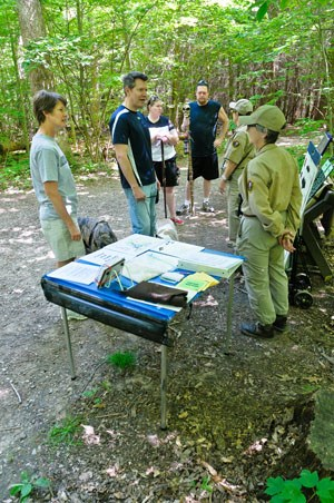 Wildlife Watchers program table display talking with visitors at a wooded trail head