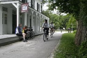 Two cyclists riding on the towpath in front of Boston Store while two cyclists sit on aporch and watch them go by.
