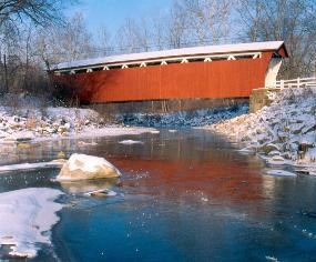 Everett Covered Bridge as seen from Furnace Run on a snow-covered, sunny winter day.