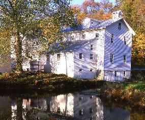 View of the a large three story grist mill and supply store along the Ohio and Erie Canal surrounded by fall foliage.