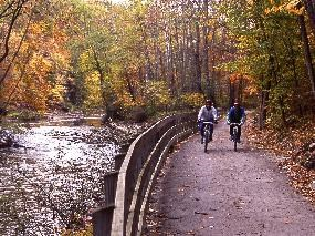 Two cyclists ride down the Ohio & Erie Canal Towpath Trail along the Cuyahoga River surrounded by autumn foliage on a fall day.