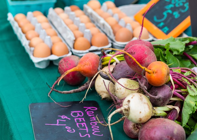 Bundles of white, purple and orange beets lie on a table in front of cartons of brown eggs.