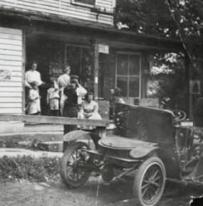 Historic photo of a family of six stand on the porch of their home with an old model automobile sitting in the foreground.