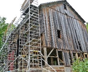 Modern photo of the historic Lindley Barn being restored. Scaffolding is stacked up along the side of the barn while the framing is being replaced.