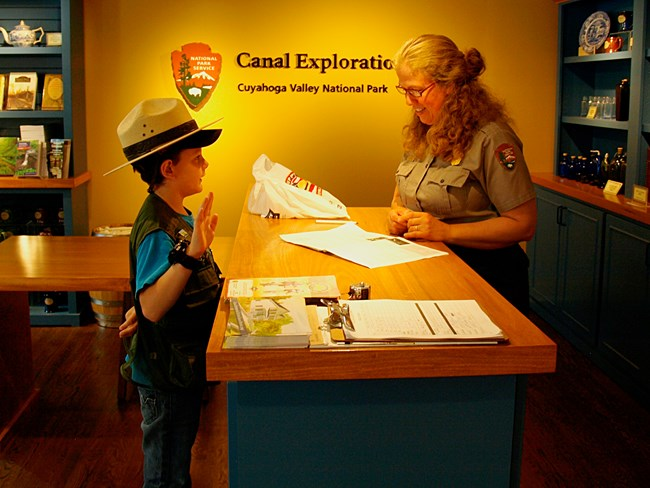 A junior ranger stands at the desk holding their right hand up and wearing a ranger hat; behind the desk, a ranger checks their work