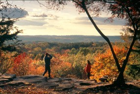 Visitors enjoying the sunset and colorful trees at the Ledges Overlook in the fall