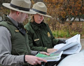 Visitor & Resource Protection Rangers discuss maps and park documents outside