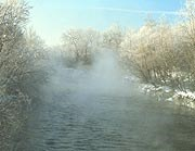 Frosted trees line the Cuyahoga River in winter, as fog rises from its surface.