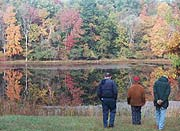 Visitors take a moment to enjoy the reflection of fall trees in the glassy waters of Sylvan Pond.