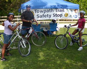 Three visitors on bikes at a Safe is Sound safety stop.