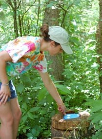Woman in tye die shirt and shorts finds a questing box hidden on a log in the woods.
