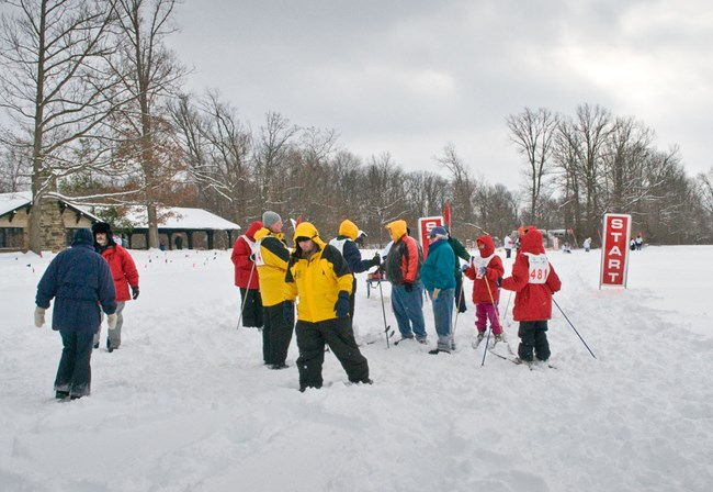 A group of cross country skiers and coaches stand, in full winter clothing, at the snow covered start line of a cross country ski race during the Special Olympics.