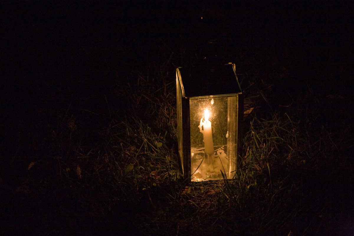 Candle lit lantern in the grass at night