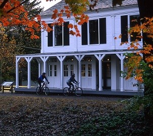 Two bicyclists pass the Boston Store Visitor Center while riding the Towpath Trail during autumn.