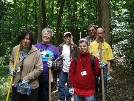 Six volunteers stand holding shovels on a newly constructed trail in a deciduous forest.