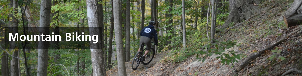 Mountain biker riding on side of steep hill.
