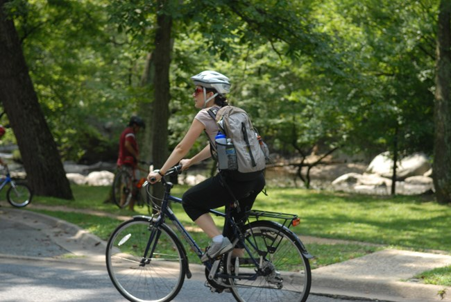A visitor riding her bike through a National Park.