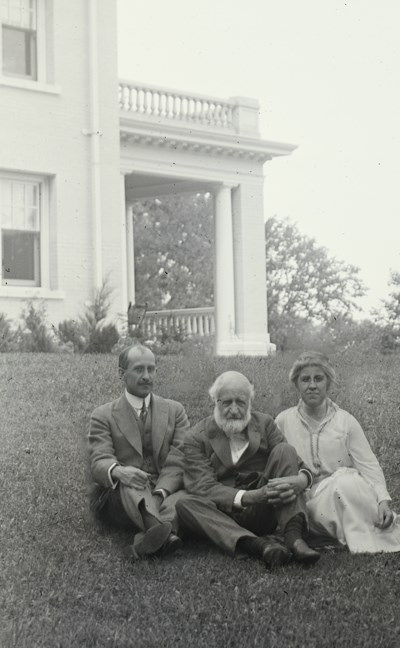 Three people sitting on a hill in front of a large house