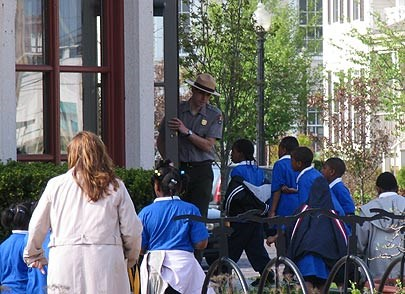 A ranger with a tan flat hat stands in a door entrance and speaks to children in blue shirts as they walk up to enter the building.