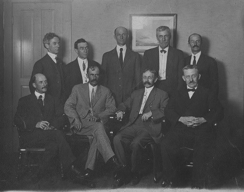 Ten men, five seated and five standing