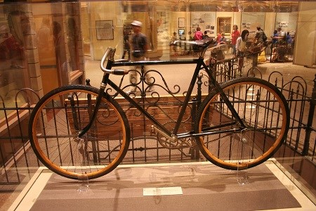 An early period bicycle on display inside of a glass case, surrounded by iron gates as people walk by.