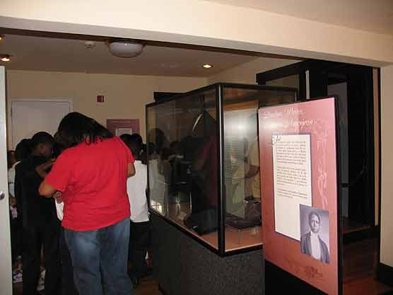 Several visitors inside the Dunbar house next to collections displayed in glass cases.