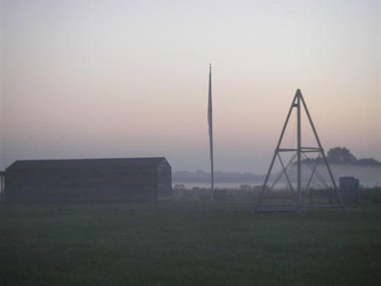 A large, one-story barn on the left, next to a triangular structure on the right with a flagpole in the middle.