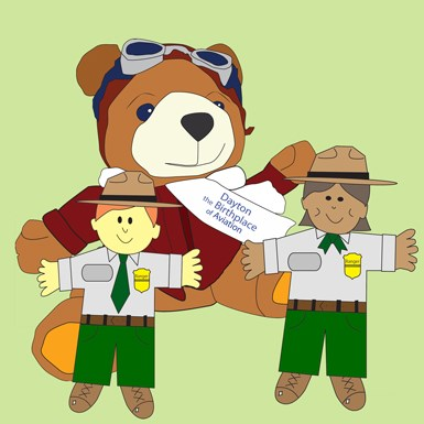 WILBEAR cartoon on a green background with flat rangers in gray shirts, green pants and brown flat hats.