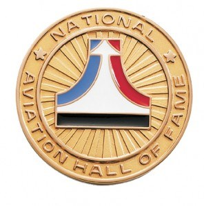 Aviation Hall of Fame logo on a gold seal with a red and blue line curving up to the top with an arrow representing a plane on top