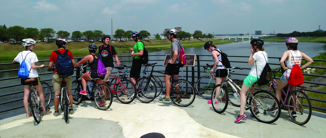 Bicyclists on their bikes overlooking the river