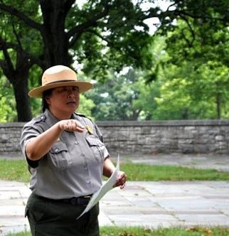 A ranger in a flat hat, in front of a stone wall, speaks to visitors out of camera view.