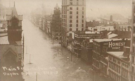 An old photo showing very high water on a street between several buildings in a downtown area of Dayton, Ohio.
