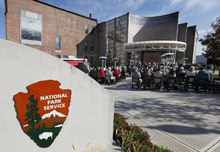 Several people seated in an open-air plaza in front of a large brick building with a sign of the NPS arrowhead logo in the foreground.
