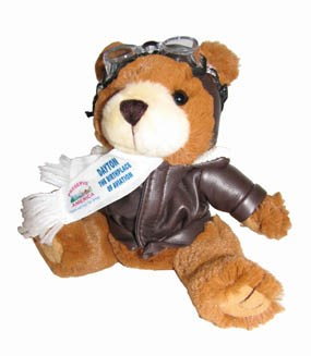 A stuffed teddy bear wearing a brown jacket and goggles on his head and a white scarf