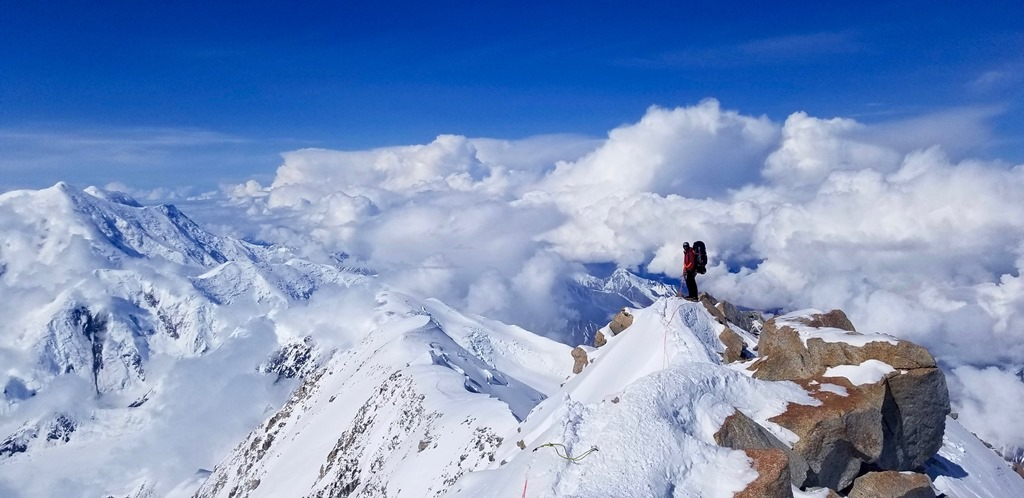 A roped climber stands on a steep rocky ridge above the clouds