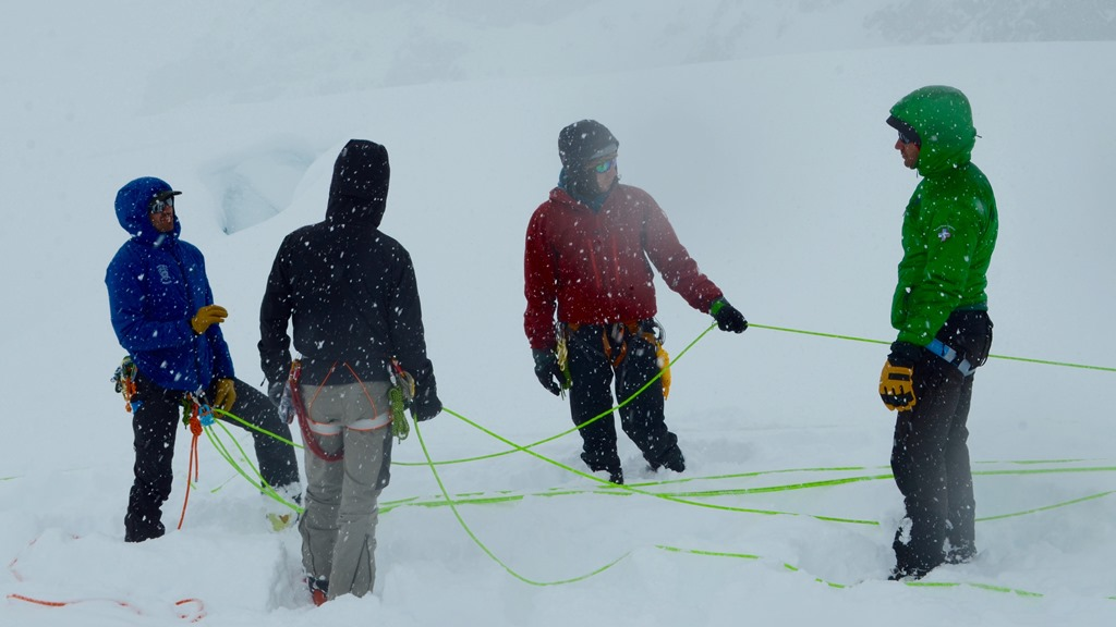 Four roped mountaineers discuss crevasse rescue skills in snowy conditions
