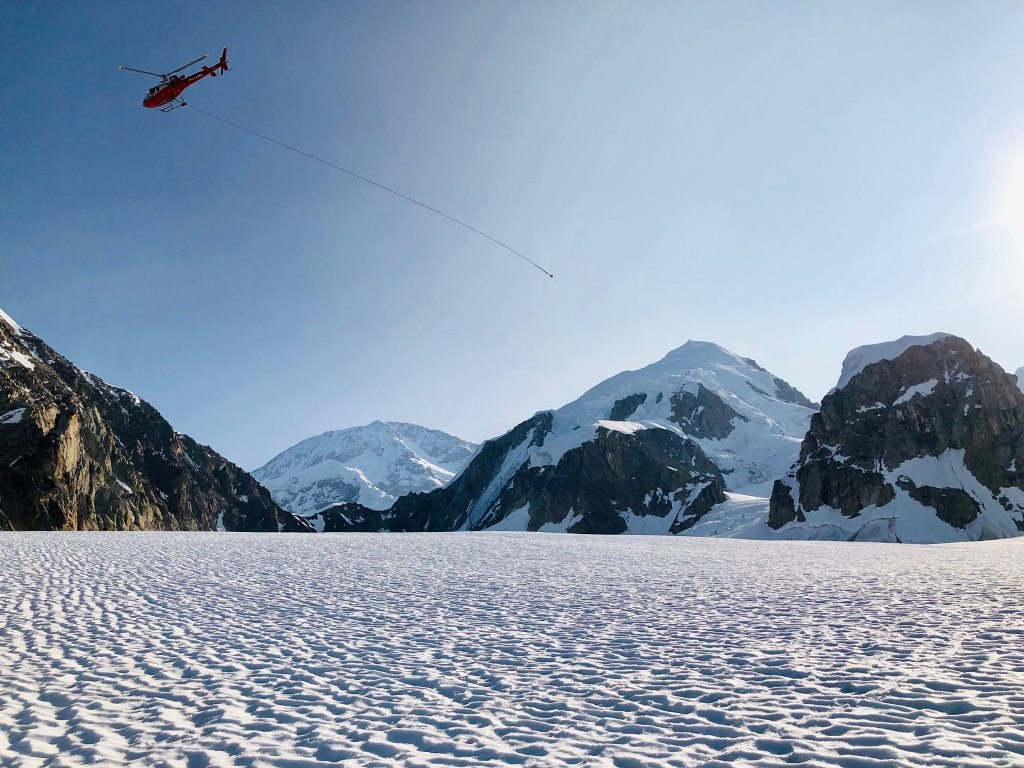 Helicopter with a long, empty rope trailing in the wind as it flies off