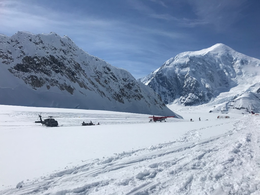 A glacier landing strip with a helicopter, an airplane, and tents