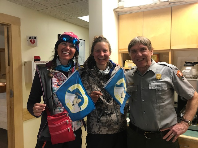 Two mountaineers recently back from Denali display their Sustainable Summits flag for packing out all human waste