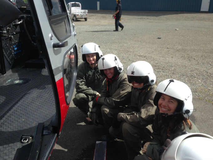Four volunteers in flight helmets crouched next to helicopter